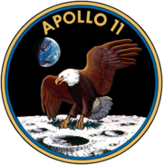 Circular insignia: eagle with wings outstretched holds olive branch on Moon with Earth in background, in blue and gold border.